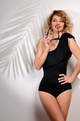 Beautiful woman wear black swinsuit on white wall with shadow palm