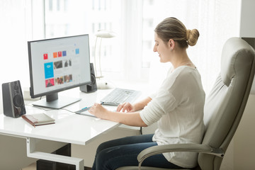 Beautiful young woman working on computer at home office