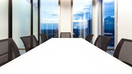 Modern meeting room with for present, large windows outside building with blue sky and clouds, twilight sky, city, tower view, soft focus
