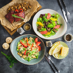 Grilled ribs with buckwheat, salad with citrus and grilled chicken liver, salad with tomato and vine in a glass. Table with food in restaurant.