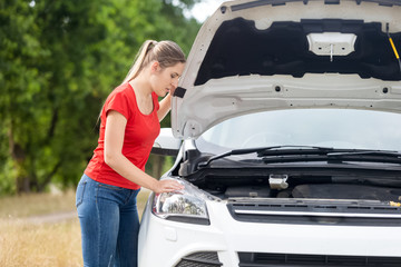 Portrait of young woman looking under the hood of her broken field on countryside road