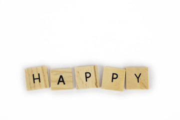Wooden tiles spelling out the word happy on an isolated white background. Inspirational and motivational!