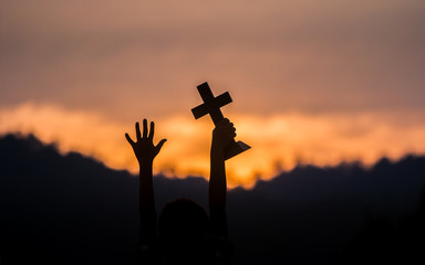 hands off children holding christian cross with light sunset background.