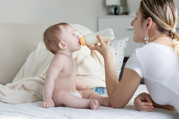 Portrait of young smiling mother feeding her baby son with milk from bottle