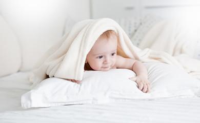 Portrait of cute baby boy lyin on white pillow under soft blanket