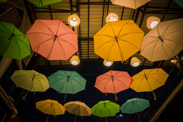 The colorful umbrellas street.Umbrellas decoration with light in dark sky background
