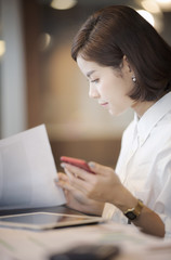 Beautiful businesswoman sitting at desk ,holding smartphone and looking at paper work
