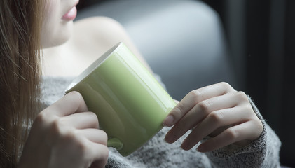 cropped image of woman hands holding green mug