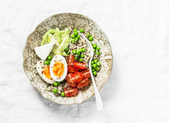 Morning savory breakfast bowl. Balanced bowl with quinoa, egg, avocado, tomato, green pea. Healthy diet food concept. Top view, on light background