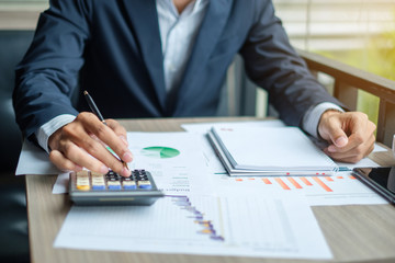 Businessman analysis maketing plan, Accountant calculate financial report, smart phone with graph chart.  Business, Finance and Accounting concepts