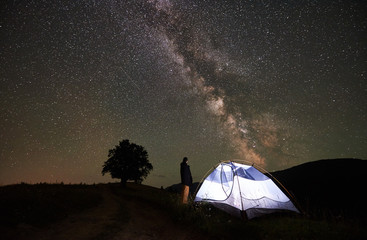 Female tourist enjoying incredible beautiful starry sky and Milky way at night camping in the mountains. Woman standing beside illuminated tent. Silhouette of big tree on background. Astrophotography