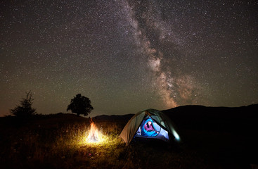 Woman hiker having a rest at night camping beside campfire in the mountains under incredible beautiful starry sky and Milky way. Girl sitting inside illuminated tent and sleeping bag. Astrophotography