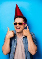 Young man in birthday hat and sunglasses on blue background