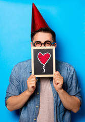Young man in birthday hat with blackboard and heart on it on blue background