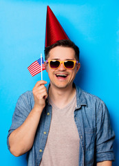Young man in birthday hat and sunglasses holding an american flag on blue background