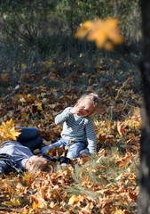 A young woman with a cute little girl  are on the yellow foliage on the ground outdoors