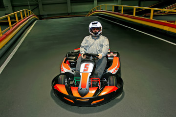 a man in helmet in the go-kart on the karting-track indoors