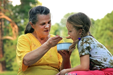 A grandmother is feeding her granddaughter by spoon from bowl outdoors