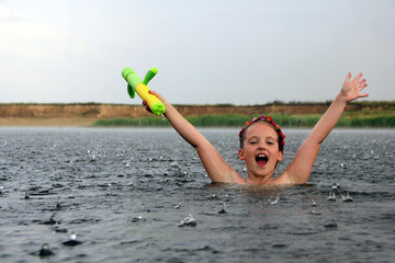 happy little girl with a water pistol bathes in a river under the rain