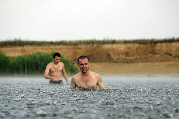 two young man are in a river under the rain