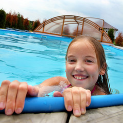 head of a smiling little girl in the pool
