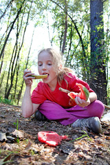 A little girl eats watermelon sitting on dry grass