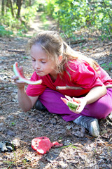 A little girl in pink clothes eats watermelon sitting on dry grass