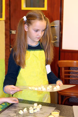 a little girl in a yellow apron holds a chopping board with dough pieces on a culinary master class