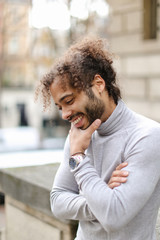 Afro american cheerful businessman wearing grey turtleneck sweater and having curly brown hair. Concept of stylish and fashionable look.