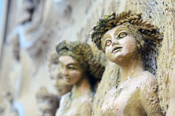 ancient stone sculptures of female images with elements of corrosion