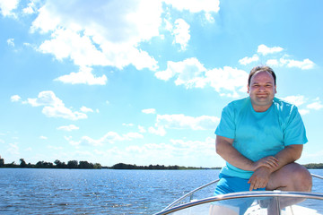 smiling man in blue clothes in a boat on a background of smooth water of a blue cloudy sky