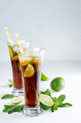 Refreshing alcohol beverage cuba libre with cola, ice, mint, lime, straw in two wet long glasses in modern white kitchen interior, copy space.