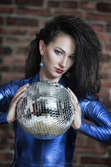 girl in a blue fitting suit with a disco ball