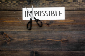 All is possible concept. Cutting the part im of written word impossible by sciccors. Dark wooden background top view copy space