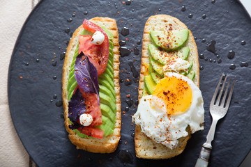 Toast with veggies,avocado, arugula, basil, tomato, mozzarella cheese  and sunny side up egg