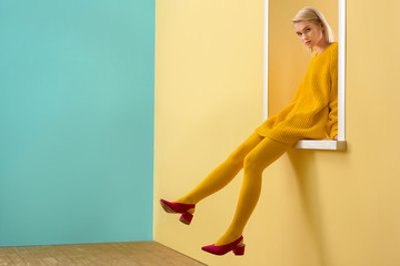 side view of stylish woman in pink shoes, yellow sweater and tights sitting on decorative window