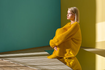 side view of pensive beautiful woman in yellow sweater and tights sitting on mirror with reflection in it