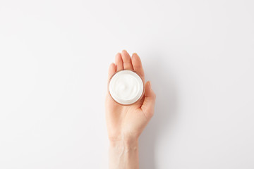 cropped image of woman holding organic cream in container
