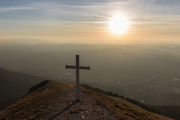 Cross on top of Mt. Serrasanta (Umbria, Italy), with warm golden hour colors and sun low on the horizon