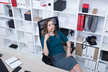Young tired girl sitting on chair in office