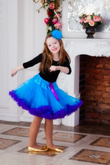 Girl with a blue bow in her hair is dancing in the room with flowers