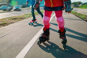 little gilr on roller skates and boy on skateboard outside