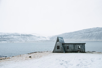 Lonely abandoned wooden house at snowy coastline in West Iceland. Winter northern scenery