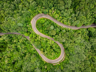 Winding curved road in the middle of the forest. Aerial shot using a drone