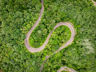 Mountain Road seen from above aerial view over a forest