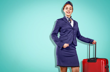Young stewardess in a blue uniform. A beautiful sincere smile. Blue background with space for your lettering.