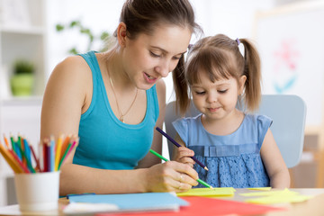 Kindergarten teacher and kid girl drawing lessons at school