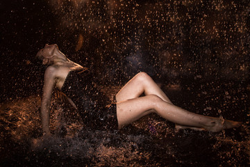Girl in black dress in water in a small pool, drops of water and dark background