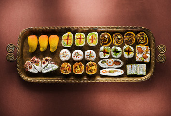Indian sweets and Mithai in a tray for Diwali festival, flat lay, top view