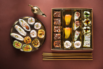 Indian sweets and Mithai in a box and a plate, insense sticks and Aladdin lamp. Diwali festival concept, flat lay, top view
